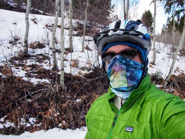 Dressed for a cold, windy day (and descending). Buff used as a face mask, softshell beanie, and puffy jacket.
